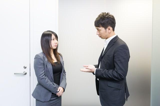 スタンディング会議中の上司と部下の写真