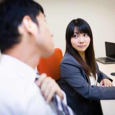 「気になる先輩の横顔を見つめる女性と気付きネクタイを締め直す上司」の写真素材