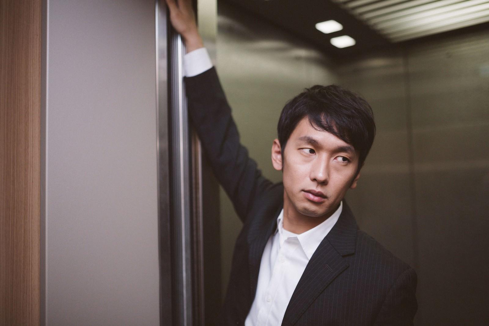 「エレベーターのドアを押さえるデキる営業」の写真[モデル:大川竜弥]