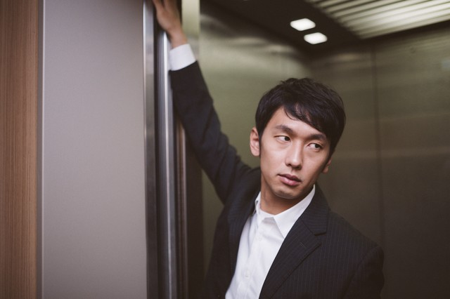 エレベーターのドアを押さえるデキる営業の写真