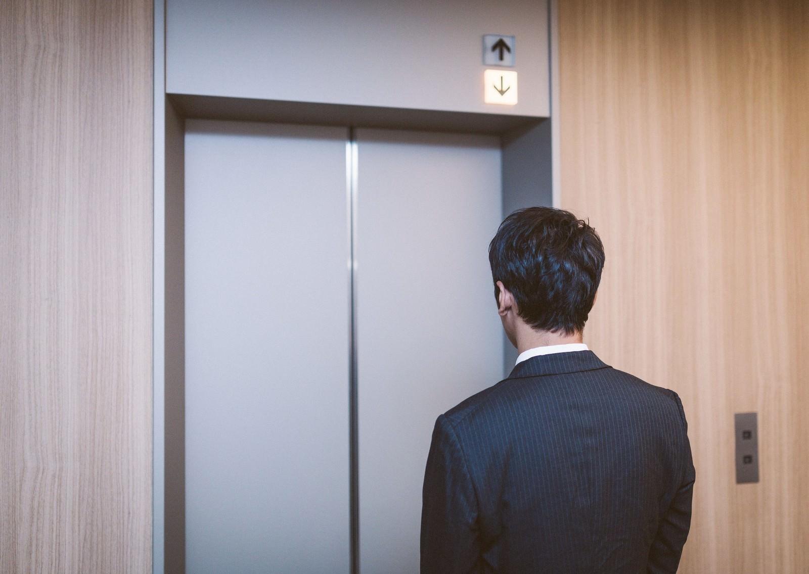 「エレベーターも給料も下降中」の写真[モデル:大川竜弥]