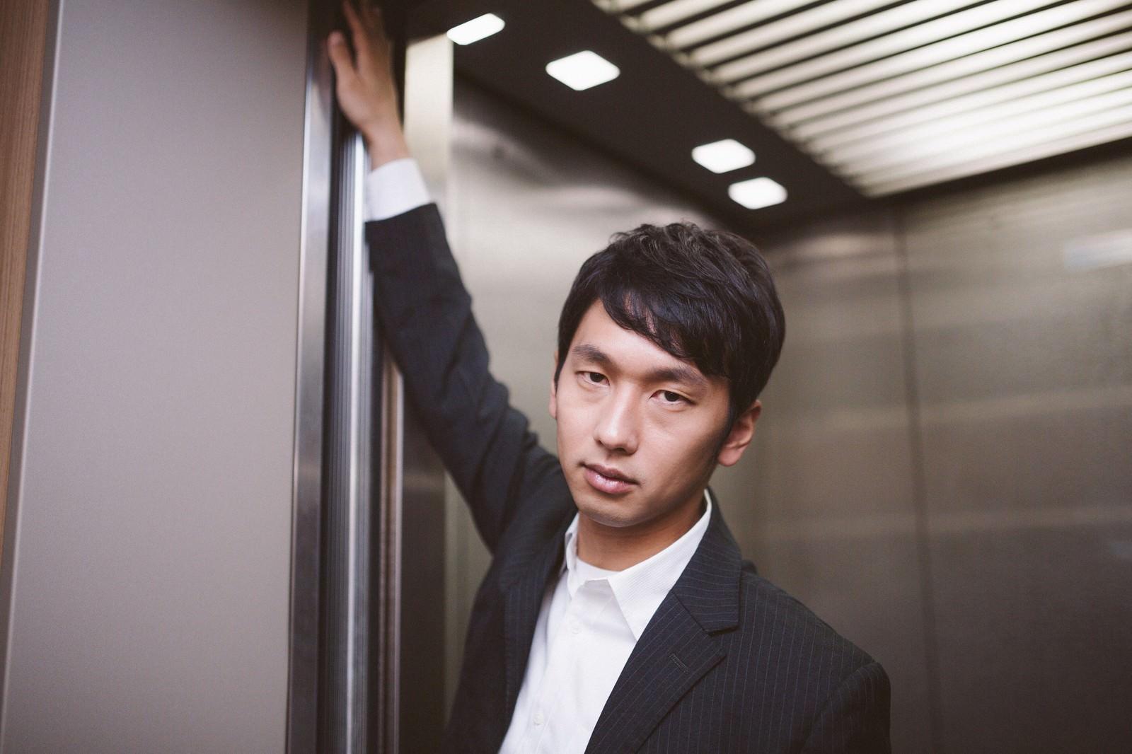 「「私、何階に行くと思います?」と難解なクイズを出す若き経営者」の写真[モデル:大川竜弥]