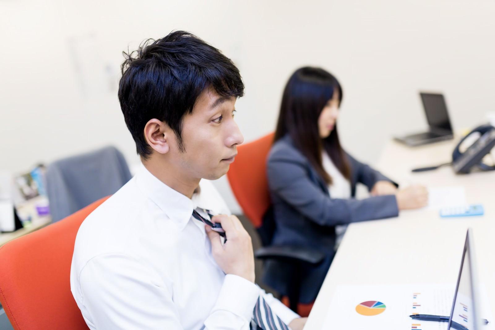 「大事な会議前にデスクでネクタイを締めるビジネスパーソン」の写真[モデル:大川竜弥 Lala]