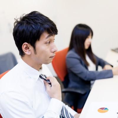 「大事な会議前にデスクでネクタイを締めるビジネスパーソン」の写真素材