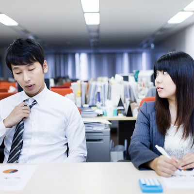 「残業中ぐちぐち愚痴を言い合う社内カップル」の写真素材
