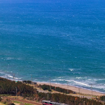 春がすみの日本海をゆく羽越線の写真