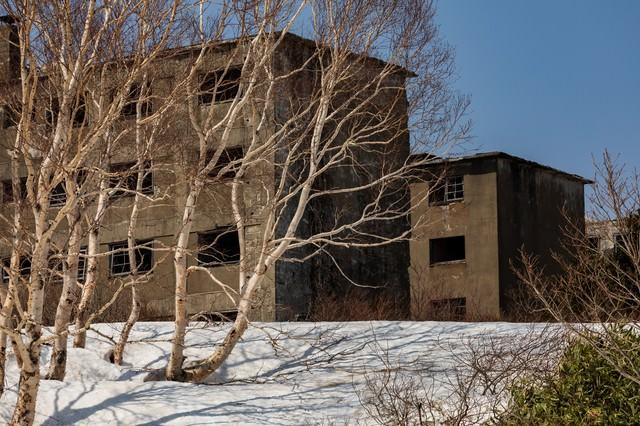 白樺と残雪の廃宿舎の写真