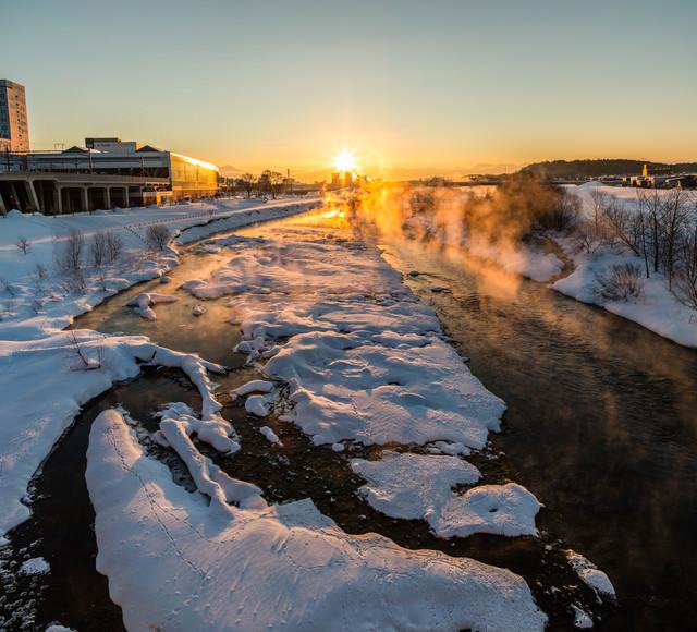 冬の川から湧き上がる蒸気霧と朝日の写真