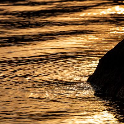 夕焼け色に染まる湖面の波紋の写真