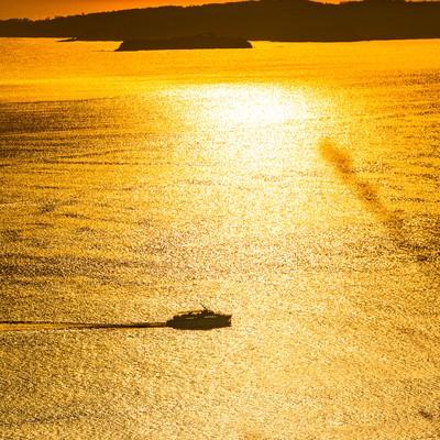 黄金色に輝く夕刻の海と渡し船の写真