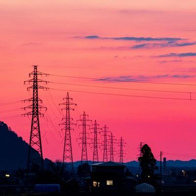 夕暮れの焼けた空と鉄塔の写真