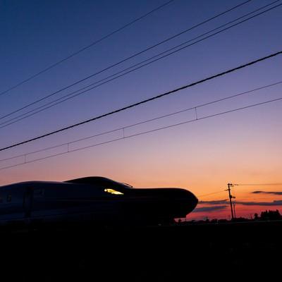 夕焼け空と特別急行列車E6系こまちのシルエットの写真