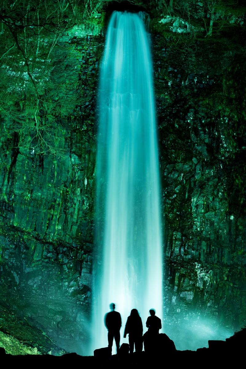「ライトアップされた玉簾の滝に見入る観光客」の写真