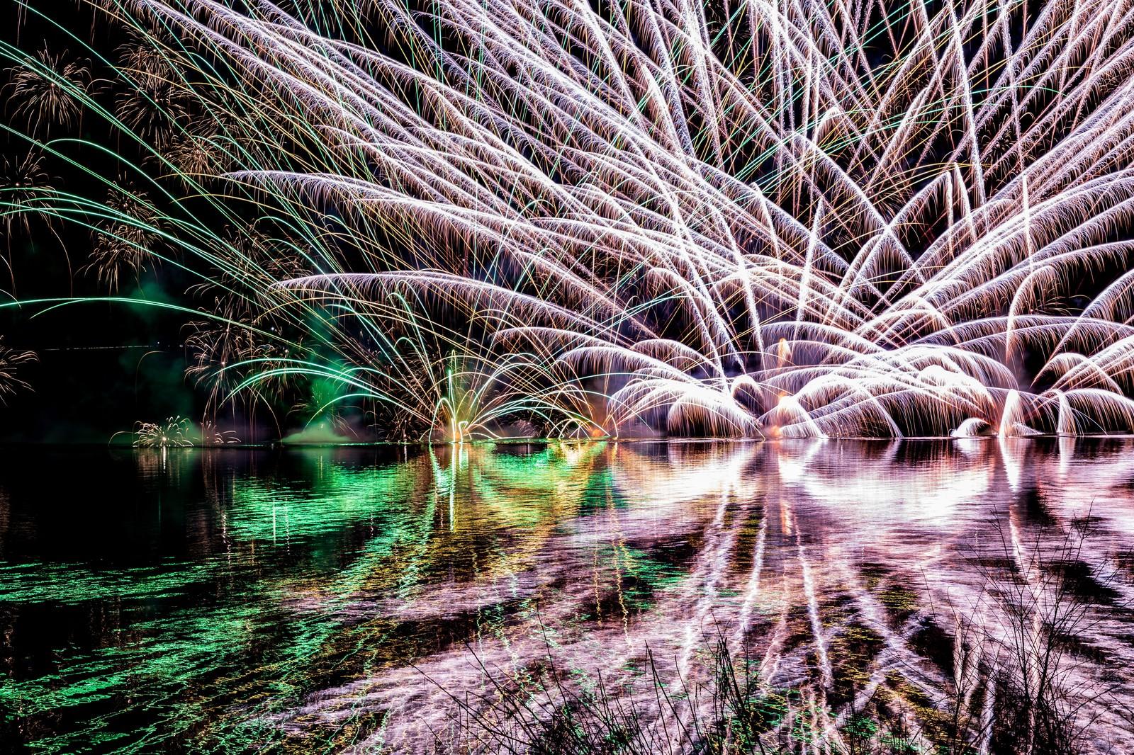 「湖面にリフレクションする水上花火(錦秋湖湖水まつり)」の写真