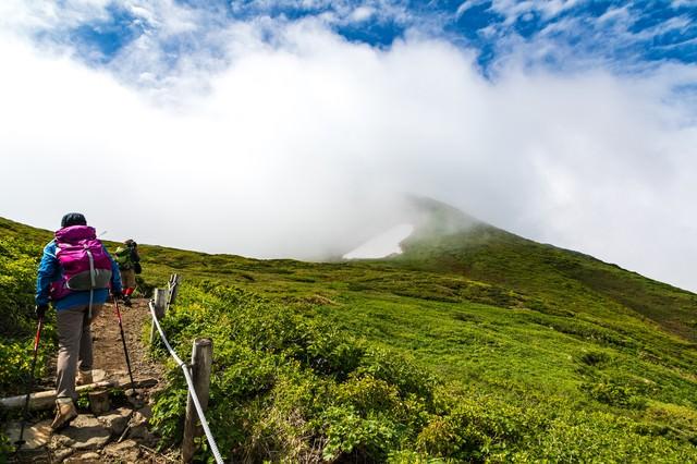 沸き立つ雲の中へと進む登山者(秋田駒ケ岳)の写真