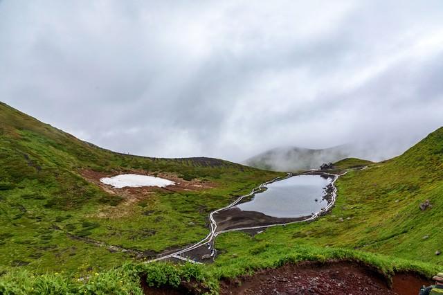阿弥陀池と眼下に迫る雲(秋田駒ケ岳)の写真