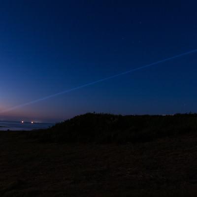 夜の入道崎灯台から放たれるレーザービームの写真