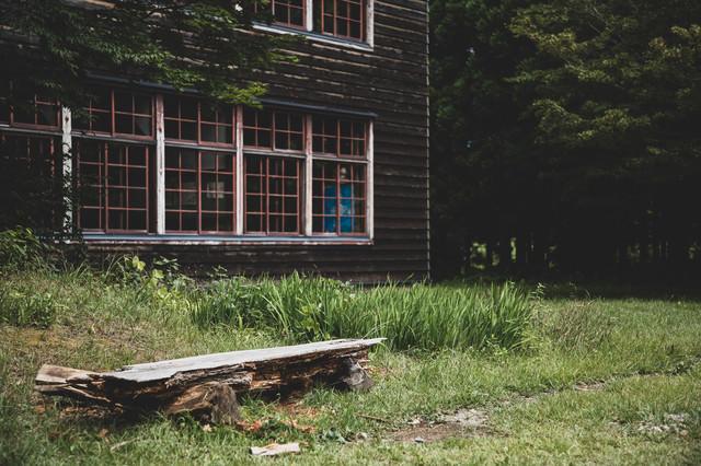 廃校の一角と朽ち果てた丸太椅子の写真