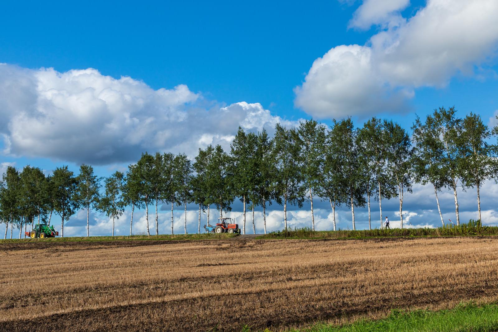 「耕された畑とトラクター」の写真