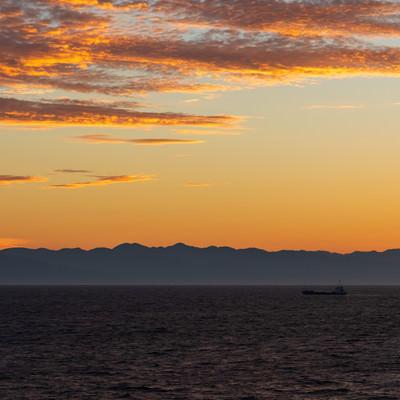 夜明け前の日本海と船の写真