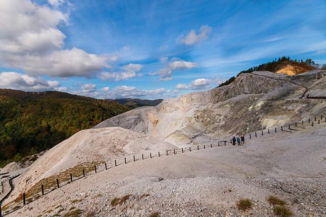 広大な川原毛地獄と登山者の写真