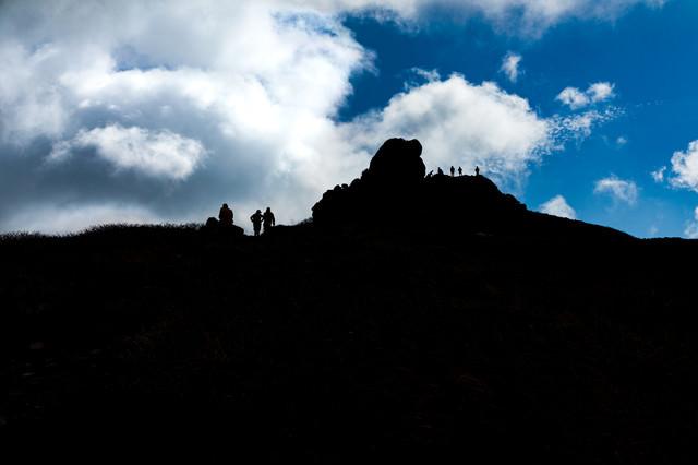 山頂に並ぶ登山者達のシルエットと沸き立つ雲(三ツ石山)の写真