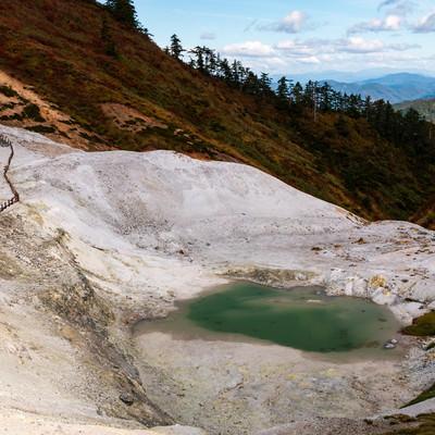 川原毛地獄の白い岩肌と池(かわらげじごく)の写真