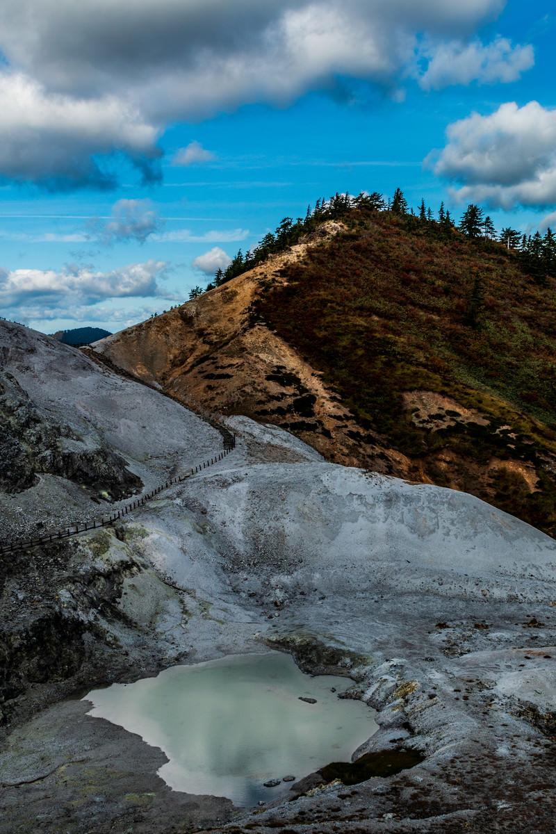 「不気味に感じる灰白色の川原毛地獄と池」の写真