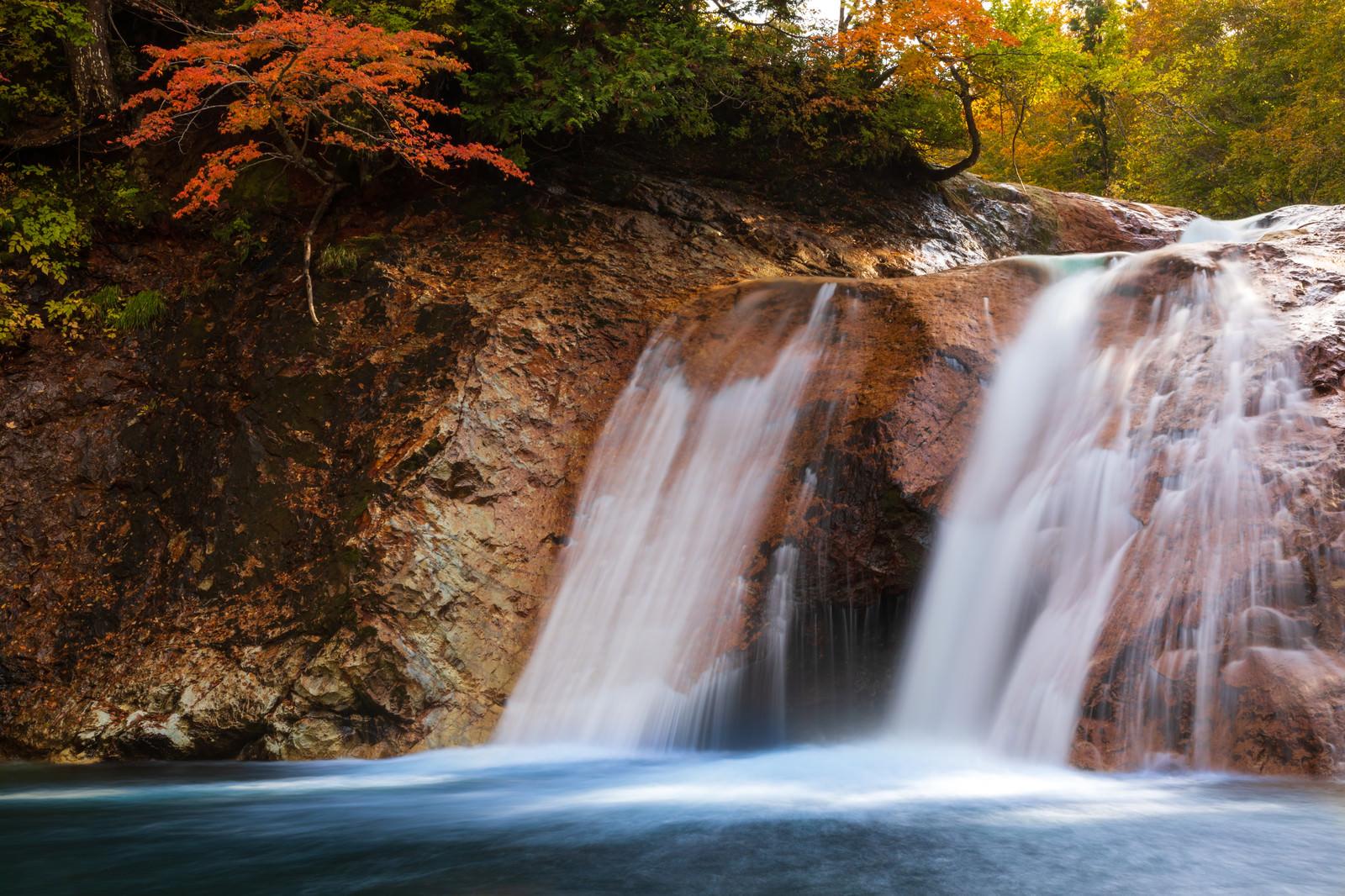 「紅葉と赤滝から落ちる水の流れ(秋田県雄勝郡東成瀬村)」の写真