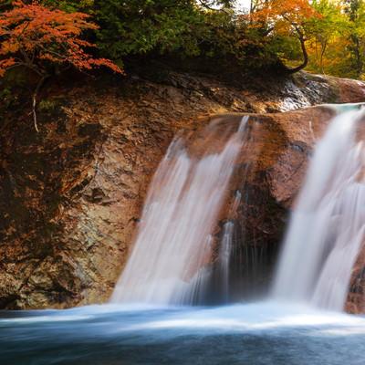 紅葉と赤滝から落ちる水の流れ(秋田県雄勝郡東成瀬村)の写真