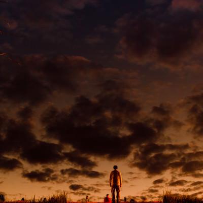 階段のある土手の上から夕焼けを拝む男性の写真