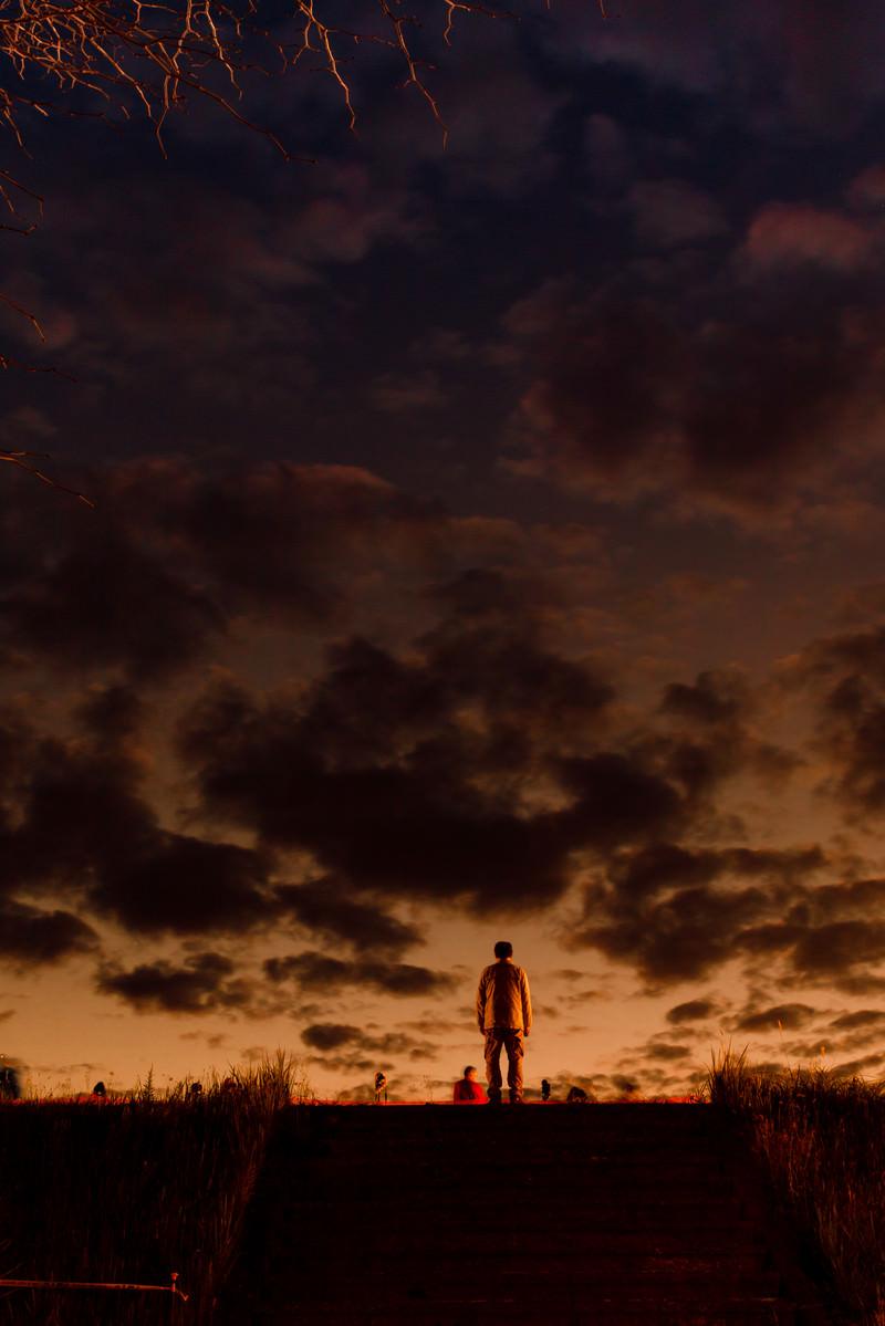 「階段のある土手の上から夕焼けを拝む男性」の写真