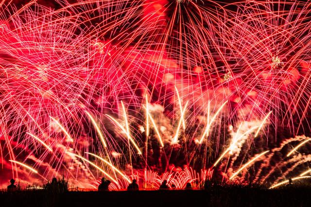花火の光跡で赤く染まる大曲の秋の夜空(秋田県大仙市)の写真