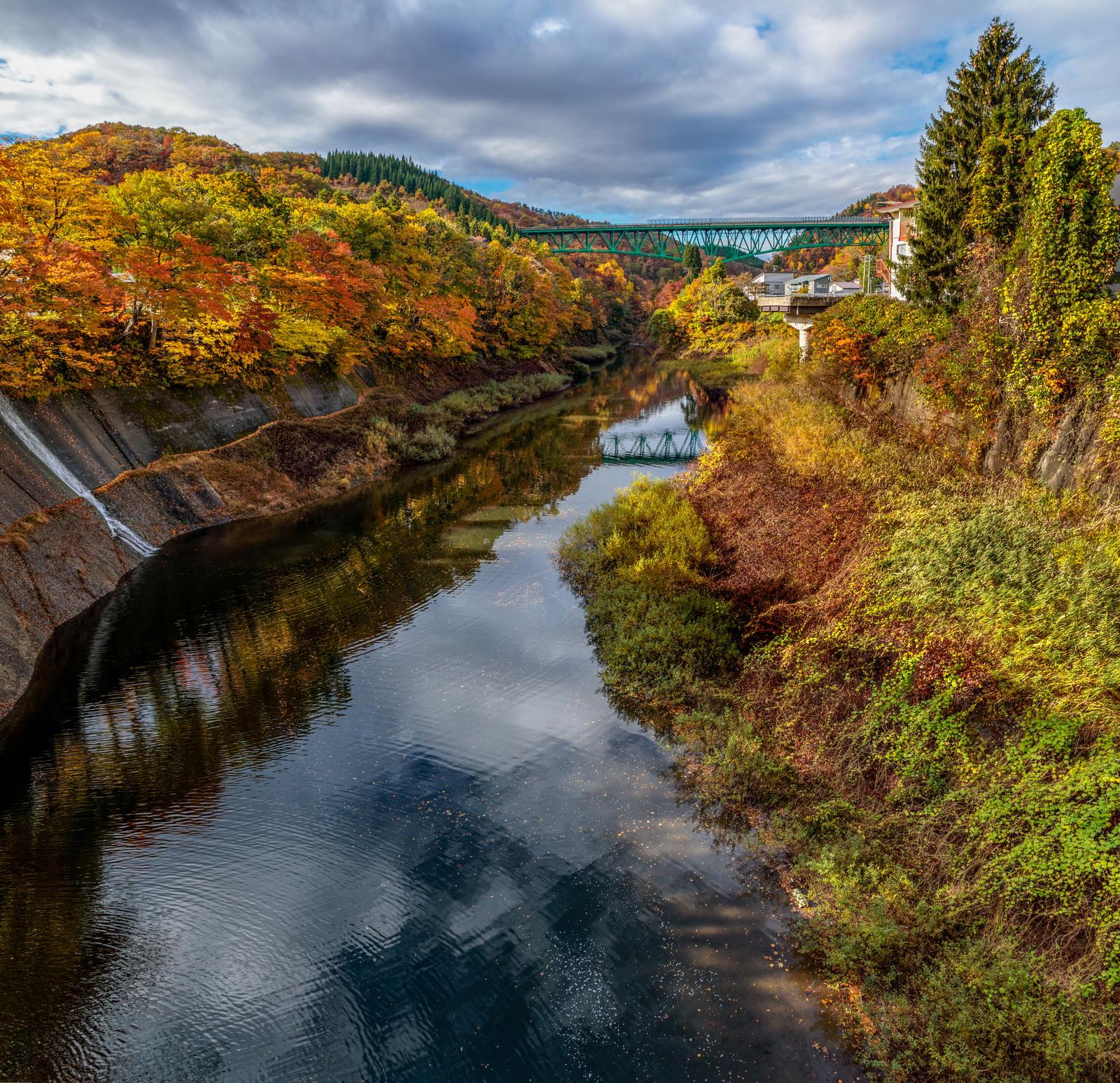 「鉄橋に向かう水路沿いの紅葉した木々とリフレクション」の写真