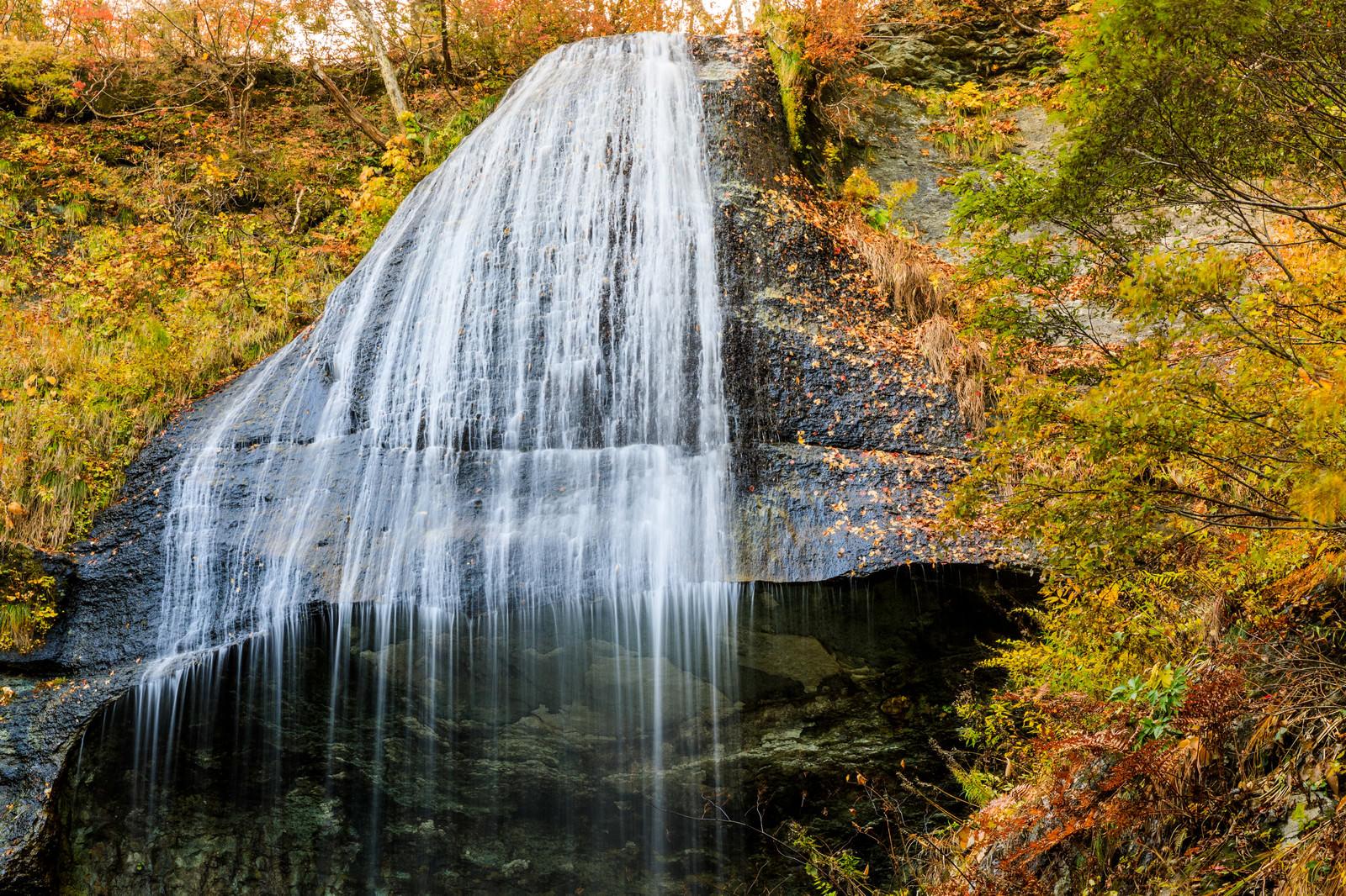 「紅葉した木々と白糸の滝(岩手県和賀郡西和賀町)」の写真