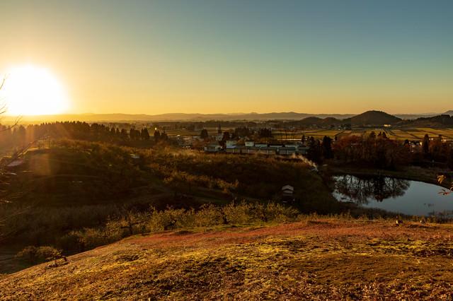 夕焼けに染まる町並みと夕日の写真