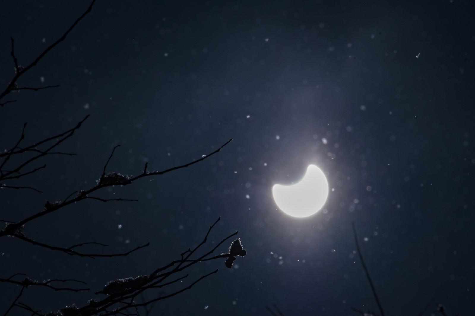 「キラキラと反射する粉雪と日食」の写真