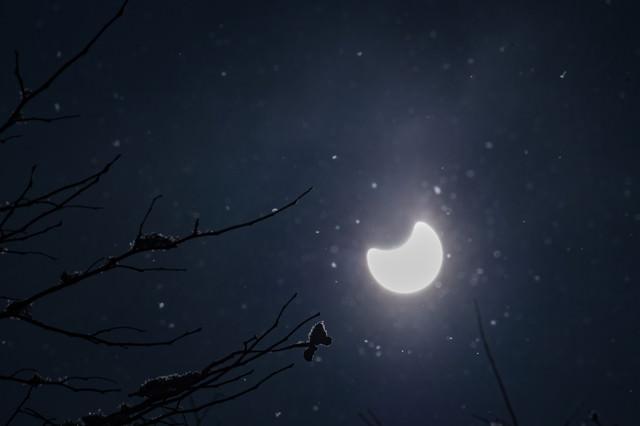 キラキラと反射する粉雪と日食の写真