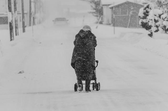 雪が降る中、移動する豪雪地帯に住む高齢者の写真