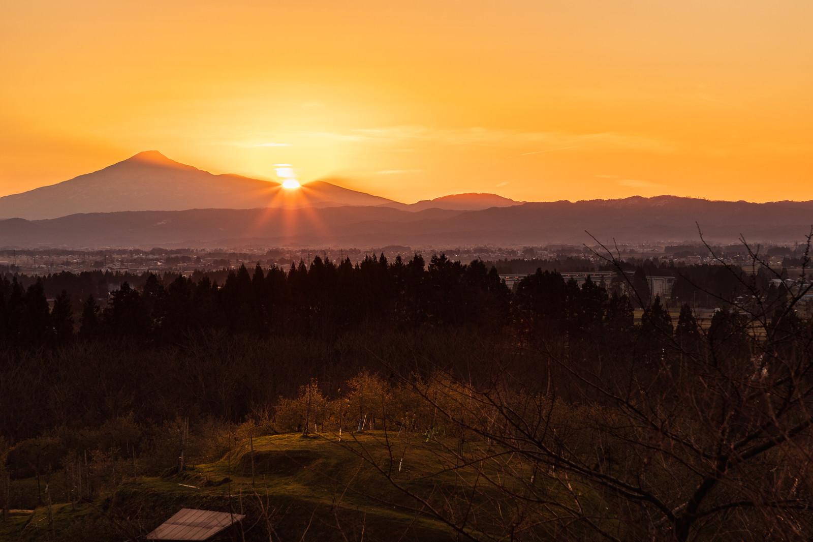 「鳥海山の裾野に沈む夕日と林檎畑」の写真