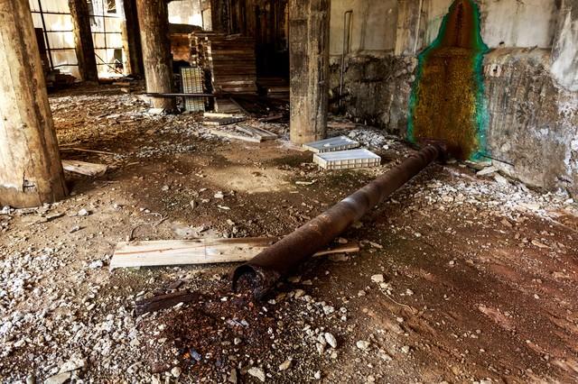 錆びて折れた配管と廃墟の写真