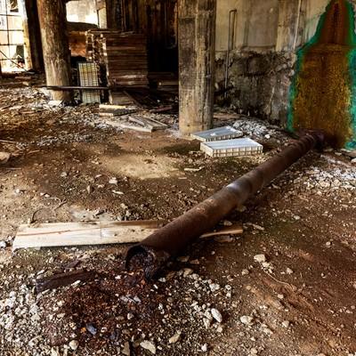 「錆びて折れた配管と廃墟」の写真素材