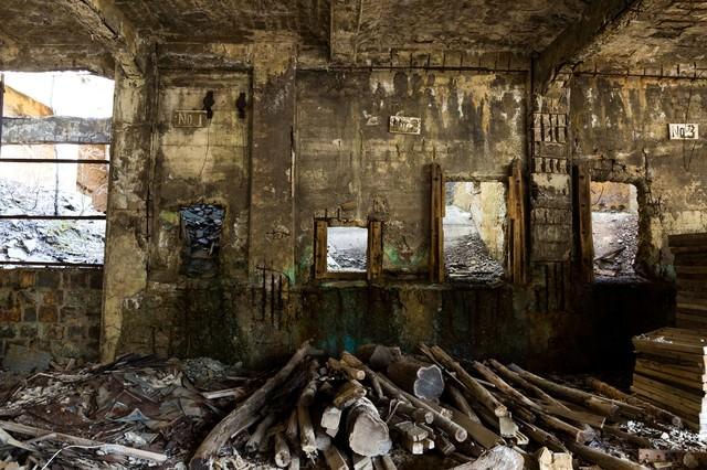 木材が置かれた廃墟の写真
