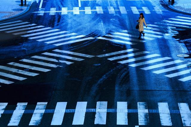 凍結した交差点と横断する女性の写真