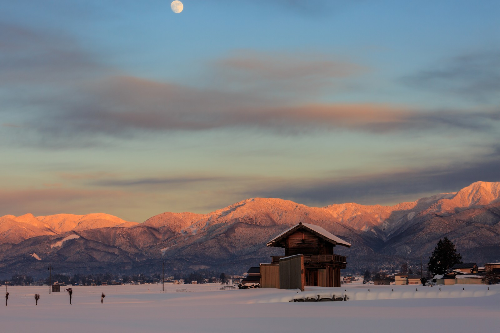 「雪に包まれた奥羽山脈と月」の写真