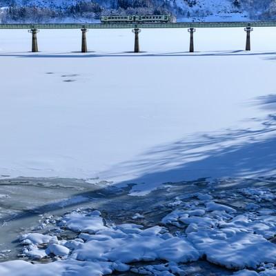 凍った湖を渡る列車(北上線)の写真