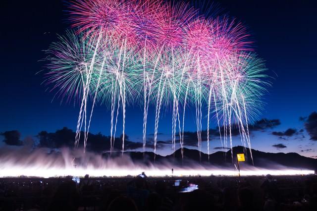 一斉に打ち上げられた花火大会の幕開けの写真