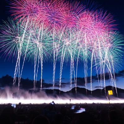「一斉に打ち上げられた花火大会の幕開け」の写真素材