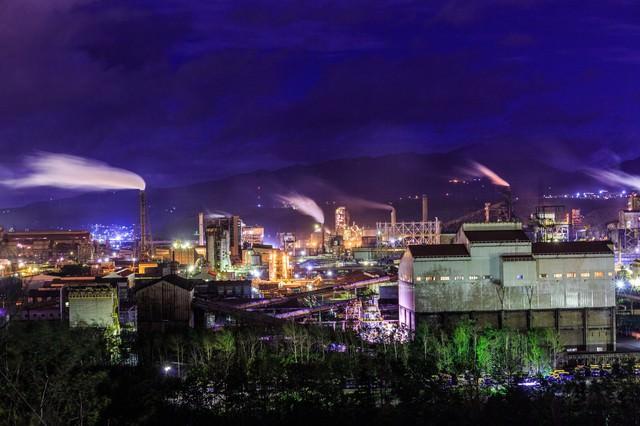 煙たなびく工場夜景の写真
