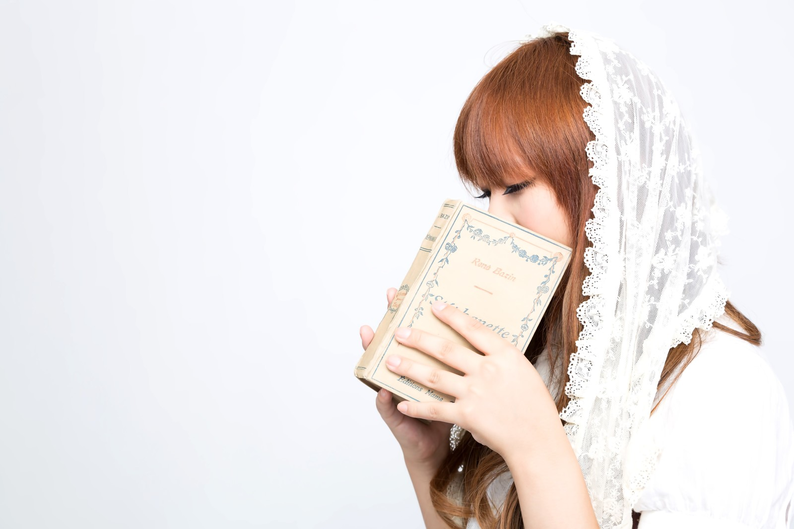 「洋書で口元を隠すガーリーな女の子」の写真[モデル:あみ]